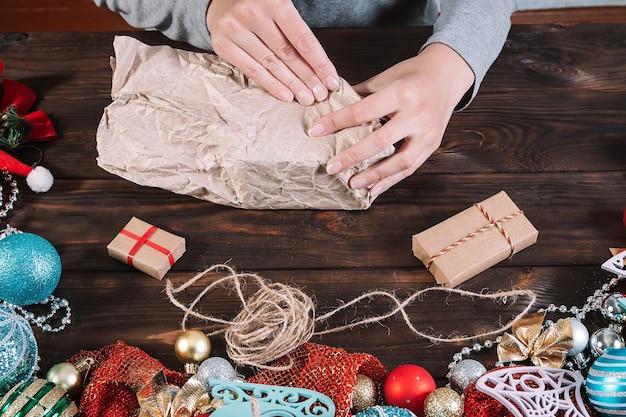Vrouw is kerstcadeautjes inpakken op een donkere houten tafel met kerstversiering