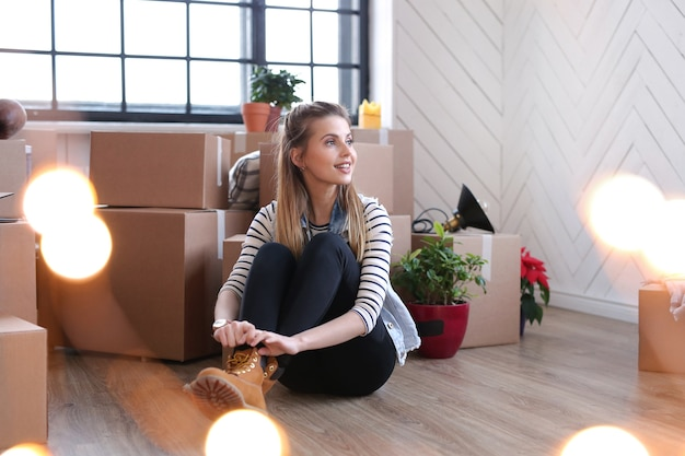 Vrouw is klaar met vrachtpakketten en zit naast de dozen op de grond