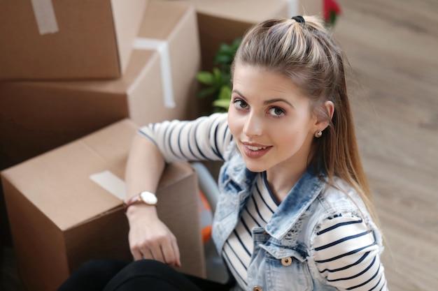 Vrouw is klaar met vrachtpakketten en zit naast de dozen