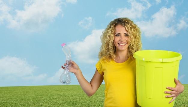 Vrouw is klaar om een plastic fles in de vuilnisbak te doen.