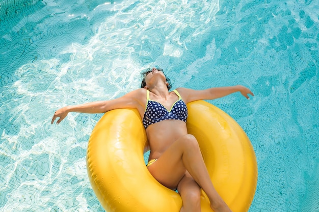 Vrouw is ontspannen in het zwembad met rubberen ring.