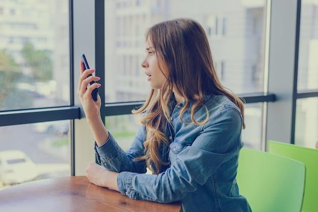 Vrouw is teleurgesteld over sms die ze van haar vriendin heeft gekregen. ze kijkt naar haar mobiele telefoon met geopende mond en verdriet.
