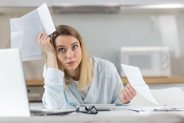 Vrouw is uitgeput en gefrustreerd met documenten van ondernemings- of gezinsbudget thuis