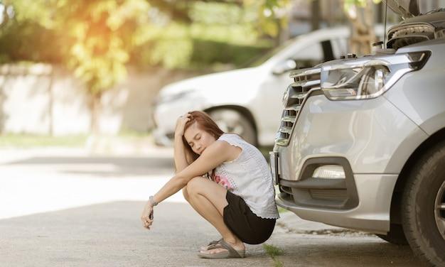 Vrouw is verdrietig vanwege een kapotte auto