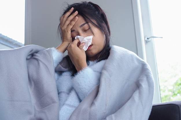 Vrouw is ziek met hoofdpijn, hoge koorts en griep, zittend onder een deken