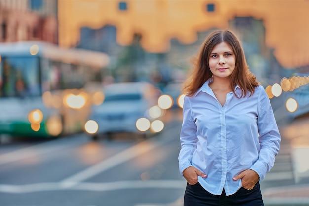 Vrouw jaar oud staat in de buurt van verkeer met verlichting door koplampen van auto's