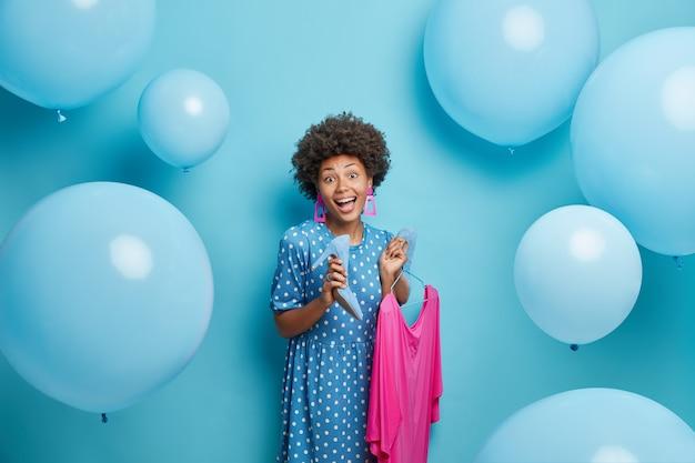 Vrouw jurken voor feest houdt roze jurk op hangers en modieuze schoenen met hoge hakken poses op blauw