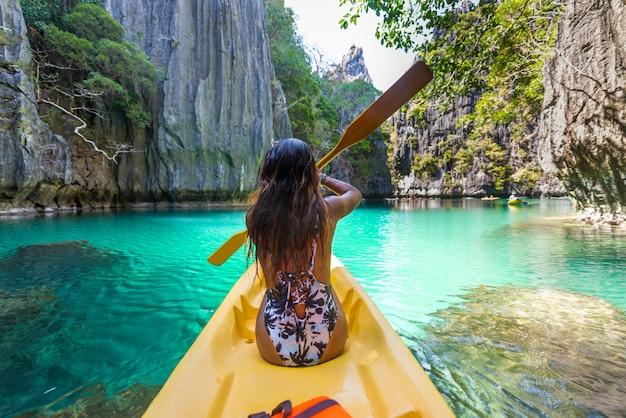 Vrouw kajakken in de kleine lagune in el nido, palawan, filipijnen - reisblogger die de beste plaatsen in zuidoost-azië verkent