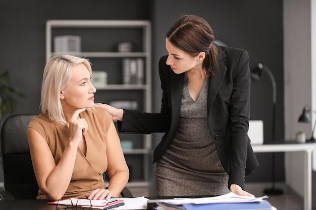Vrouw kalmeert haar ontslagen volwassen collega in kantoor
