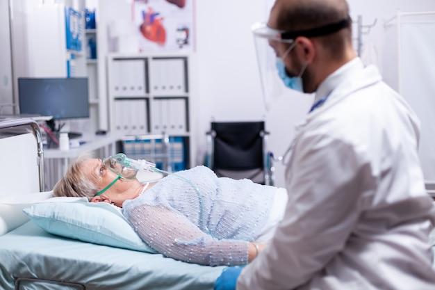 Vrouw kan niet ademen zonder zuurstofmasker terwijl ze in het ziekenhuis ligt en arts die naast haar zit met een beschermingsmasker tegen het coronavirus als veiligheidsmaatregel