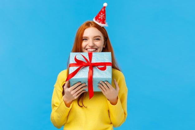 Vrouw kan niet wachten geven broer of zus haar geschenk, glimlachend dragen schattig kerst verpakt cadeau