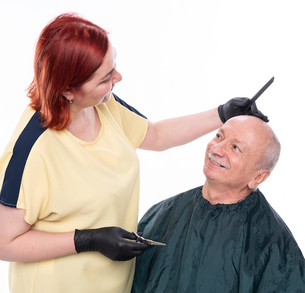 Vrouw kapper haar knippen tot een senior man