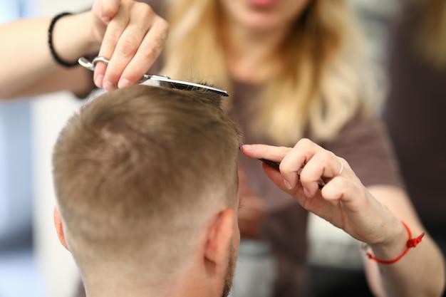 Vrouw kapper knipt iemands haar in een schoonheidssalon.