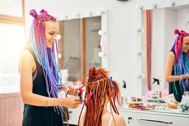 Vrouw kapper met gekleurde afro vlechten weeft naar meisje gember dreadlocks hippie stijl haar weefproces met kanekalon schoonheidssalon diensten zomer licht