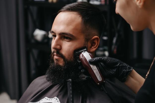 Vrouw kapper trimmen baard aan blanke man.