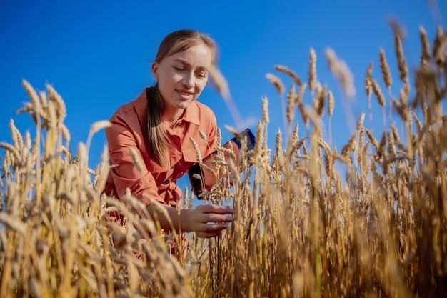 Vrouw kaukasische technoloog landbouwingenieur met tabletcomputer op het gebied van tarwe kwaliteitscontrole