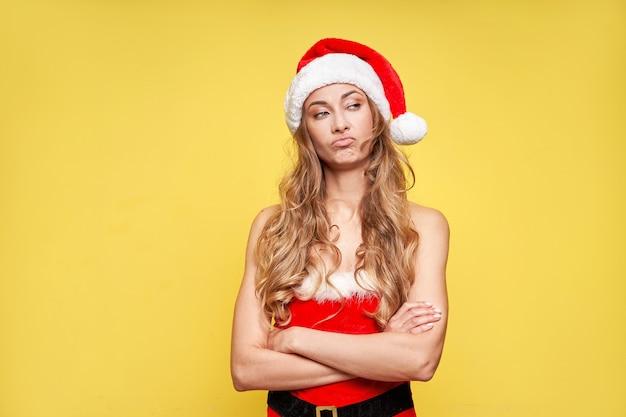 Vrouw kerst kerstmuts gele studio achtergrond met smartphone in de hand