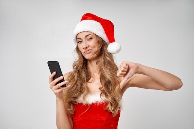 Vrouw kerst kerstmuts witte studio achtergrond met smartphone in de hand