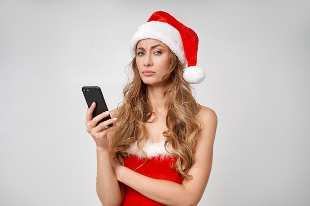 Vrouw kerst santa hat witte studio achtergrond met smartphone in de hand?