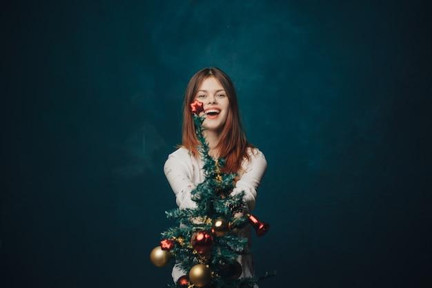 Vrouw kerstboom studio poseren