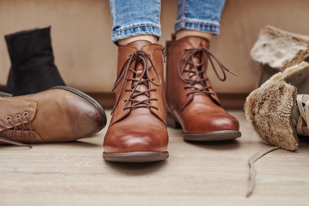 Vrouw kiest comfortabele bruine leren schoenen uit een heleboel verschillende paren
