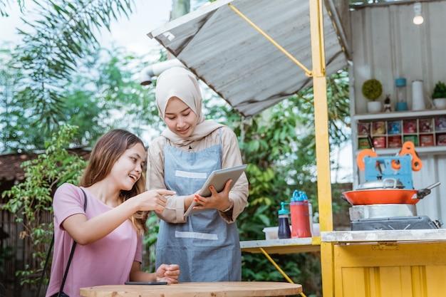 Vrouw kiest eten een menu dat een verkoper bij een kleine eetstalletje brengt