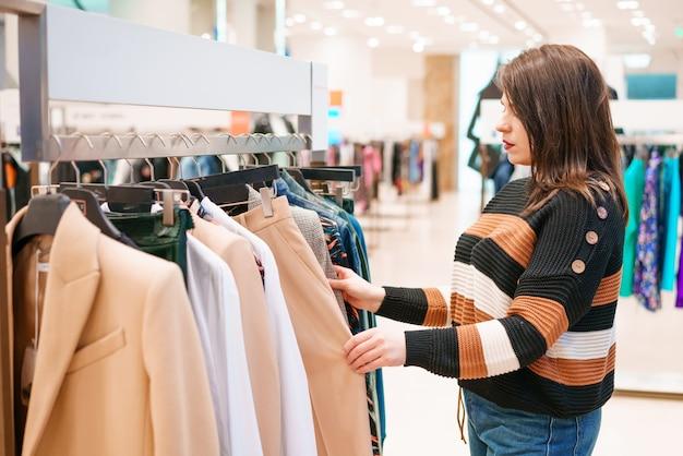 Vrouw kiest kleding in een winkel