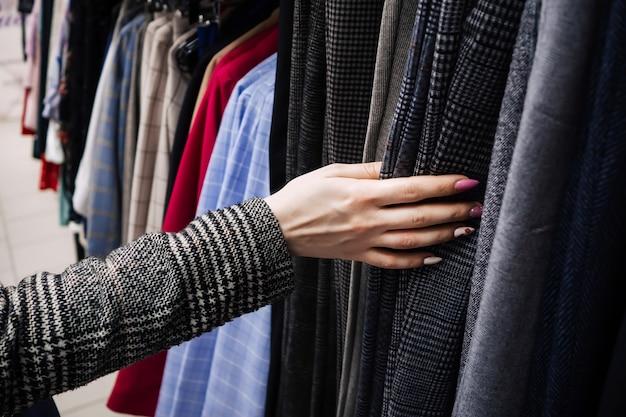 Vrouw kiest kleding met haar hand in de winkel