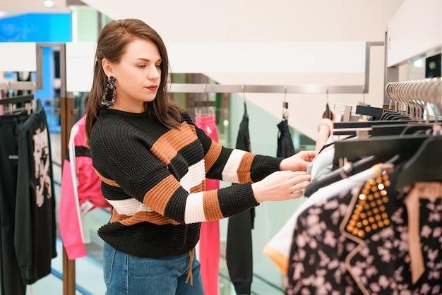 Vrouw kiest kleren in een winkel