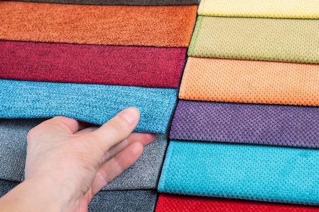Vrouw kiest monsters van gekleurde stof op tafel close-up