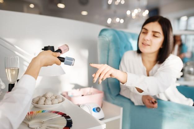 Vrouw kiest nagellak in schoonheidssalon, manicure en pedicure procedure.