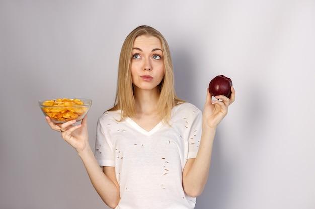 Vrouw kiest tussen chips en appel op witte muur