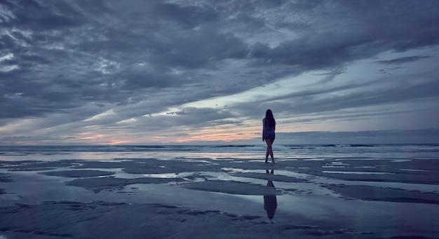 Vrouw kijken naar de zonsondergang op het strand. catedrales-strand aan de kust van galicië