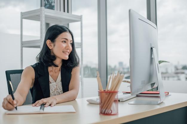 Vrouw kijken naar desktop computer en aantekeningen maken