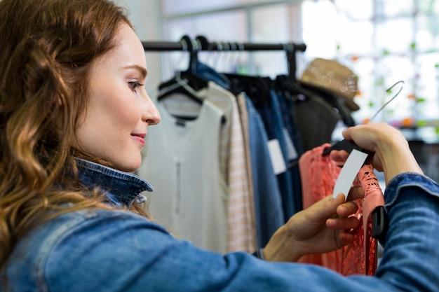 Vrouw kijken naar prijskaartje van kleding