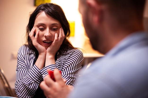 Vrouw kijkt blij naar verlovingsring tijdens huwelijksaanzoek terwijl ze een romantisch diner heeft. man vraagt zijn vriendin ten huwelijk in de keuken tijdens een romantisch diner. gelukkige blanke vrouw die lacht be
