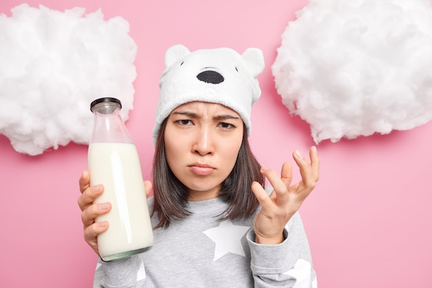 Vrouw kijkt boos naar de camera heeft een slecht humeur in de ochtend gekleed in pyjama houdt een glazen fles melk vast die ontbijt gaat maken geïsoleerd op roze