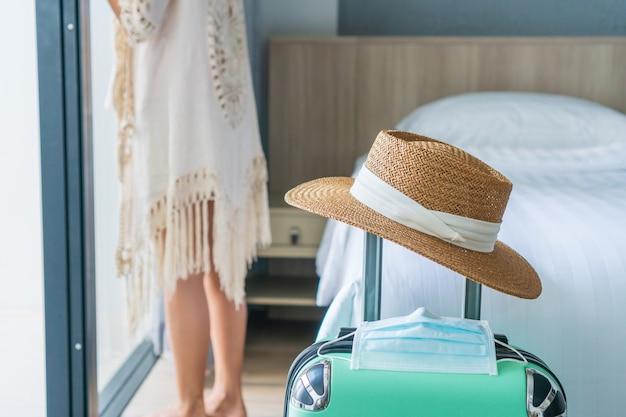 Vrouw kijkt buiten het raam met bagage, strooien hoed en gezichtsmasker
