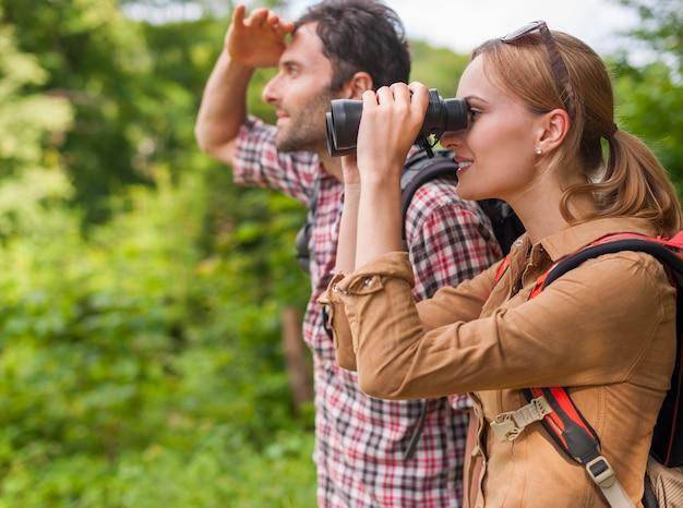 Vrouw kijkt door de verrekijker. wandeltijd