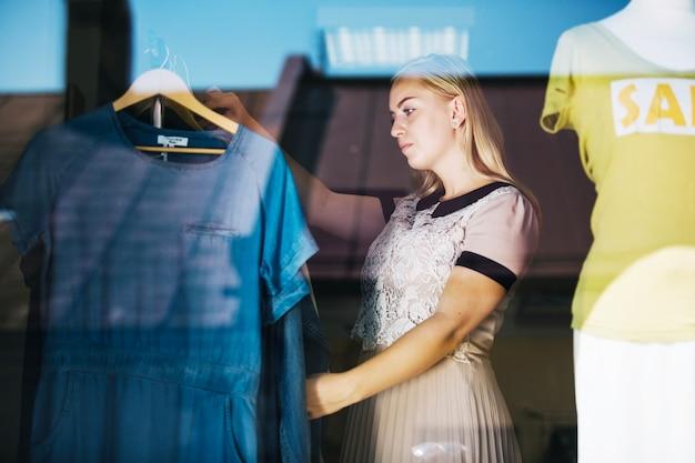 Vrouw kijkt door kleding op klerenrail