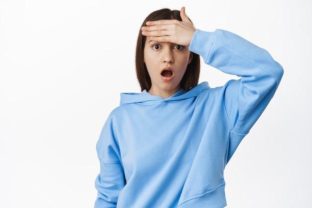 Vrouw kijkt geschokt en geschrokken, houdt hand op voorhoofd, hijgt en staart bezorgd en verontrust naar voren, hoort slecht nieuws, staande over witte muur