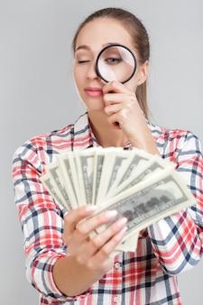 Vrouw kijkt in vergrootglas op dollarbiljetten