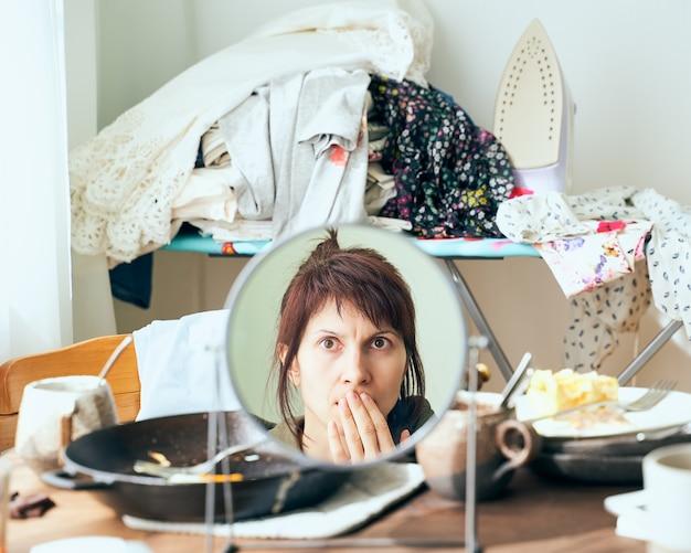 Vrouw kijkt met afgrijzen en schrik naar zichzelf in de spiegel tegen de rotzooi