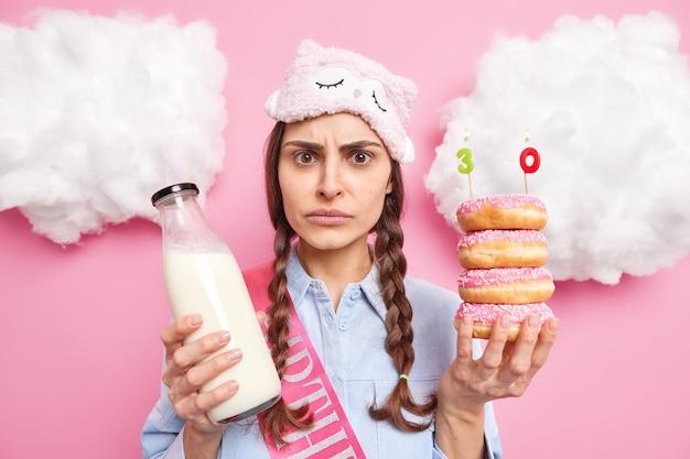 Vrouw kijkt met bezorgde uitdrukking viert 30e verjaardag houdt stapel donuts en melk draagt slaapmasker verjaardagslint geïsoleerd op roze
