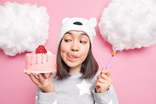 Vrouw kijkt met verleiding naar heerlijke aardbeientaart likt lippen houdt tandenborstel wil gezonde tanden