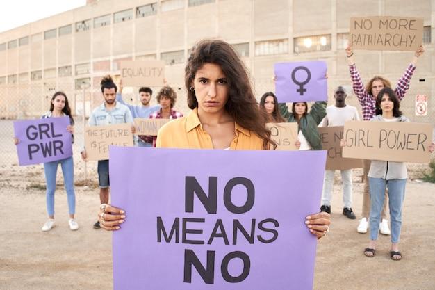 Vrouw kijkt naar camera met banner activisten demonstranten feminisme marsdemonstratie