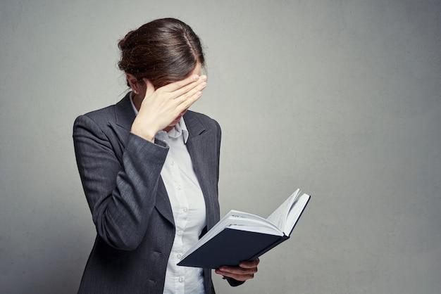 Vrouw kijkt naar dagboek en bedek haar gezicht met de hand