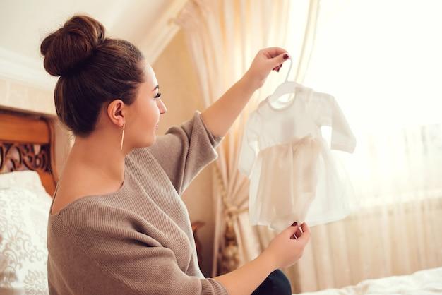 Vrouw kijkt naar de kleine jurk voor dochter. moeder bereidt zich voor op de bevalling tijdens de zwangerschap.