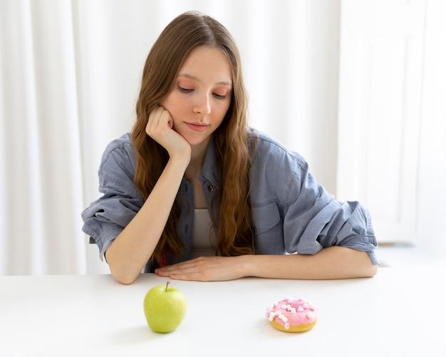 Vrouw kijkt naar donut en appel