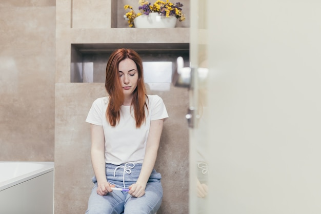 Vrouw kijkt naar een snel positief of negatief resultaat zwangerschapstest
